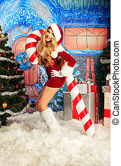 woman and candy - Beautiful young woman in Santa Claus...