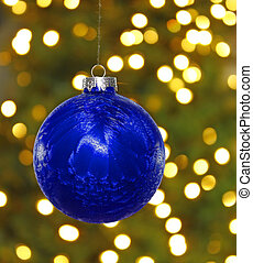 A big blue hanging Christmas ball decoration in front of a...