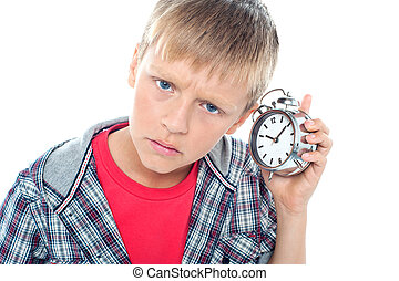 Confused young kid holding time piece close to his ear