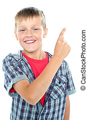 Young boy posing on white background Pointing finger towards...