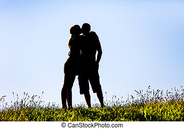 silhouette of a woman kissing a man