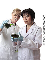 Laboratory workers - People, pouring liquid from a beaker...