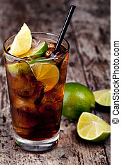 Cuba Libre Drink with lime on a wooden table