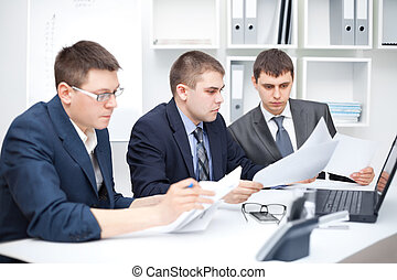 Team of young business men doing some paperwork together at...