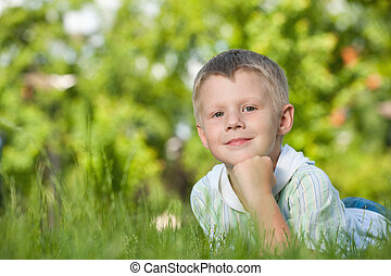 Pensive boy on the green grass - A pensive boy is lying on...