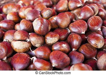 Sweet chestnuts - marron in wicker basket- as background,...