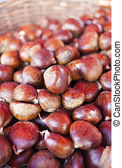 Sweet chestnuts - marron in wicker basket- as background,...