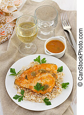 fish with sauce and boiled rice and glass of wine