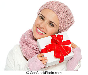 Happy woman in knit winter clothing holding Christmas...
