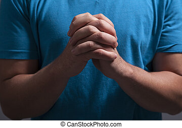 Clasped Praying Hands - A man clasps his hands and prays...