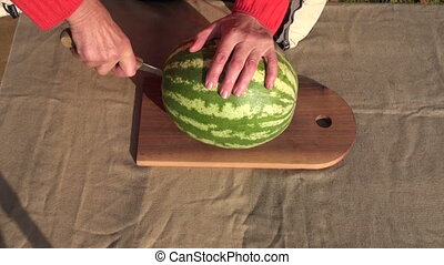 pensioner hands cutting watermelon