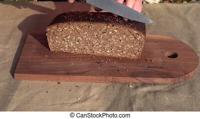 grandmother  cutting browm bread
