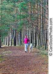 The woman with a dog run in a forest park