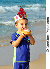 Jewish Holidays Hanukkah -Chanukah - Young Israeli boy eats...