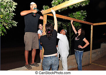 Sukkot Jewish Holiday in Israel - An Israeli family are...