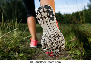 Woman and running shoes in forest, exercising in nature -...
