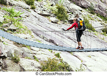 Woman trekking with backpack crossing bridge - Woman hiking...