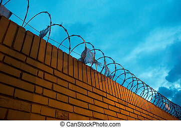 Brick Fence with Barbed Wire - A yellow brick fence with...