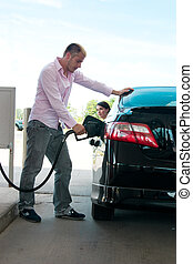 Road Trip - Pumping Gas - A young man pumps gas in his car...