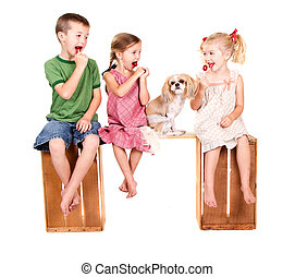 Three kids sitting on a bench eating lolli pops