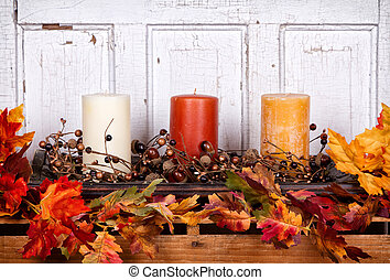 Autumn still life with candles and leaves with an antique...