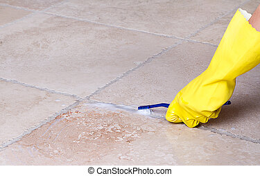 Cleaning tile grout with toothbrush - gloved hand cleaning...