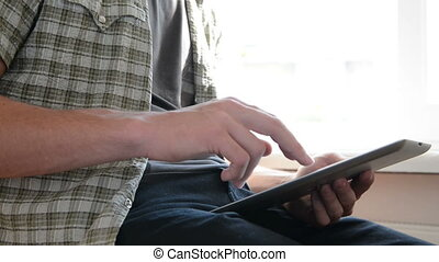Youth man works with a tablet pc