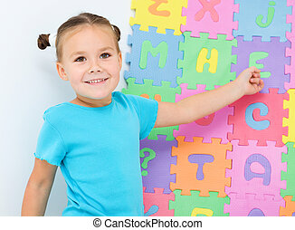 Little girl is showing letter E on the alphabet - Cute...