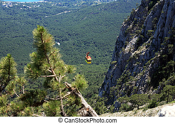 Aerial Ropeway - Yellow overhead cable car on background...