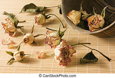Dried rosebuds scattered from wooden bowl - Dried rosebuds...