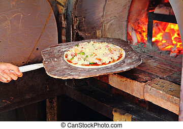 Chef placing pizza in wood fire oven