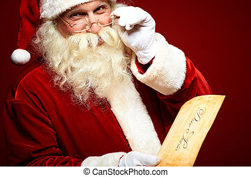 Santa with letter - Portrait of happy Santa Claus holding...