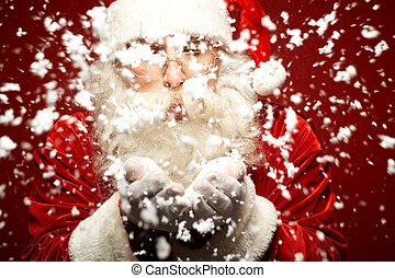 Making snowfall - Photo of Santa Claus in eyeglasses blowing...