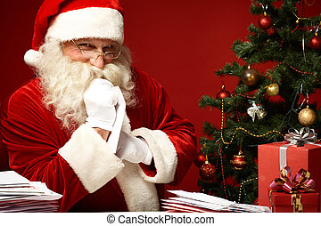 Choosing xmas letter - Portrait of happy Santa Claus looking...