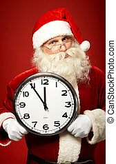 Santa with clock - Photo of Santa holding clock showing five...