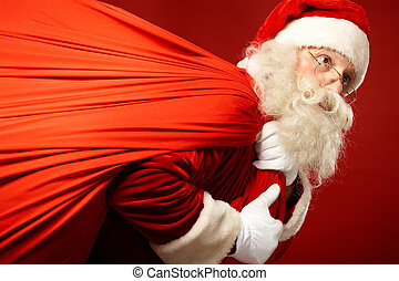 Carrying presents - Portrait of Santa Claus carrying huge...