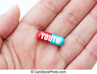 Pill of youth - Hand holding a pill labelled with youth