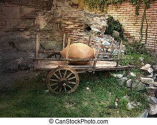 The old bullock cart with a clay jug on a background of...