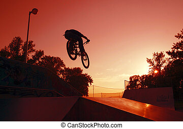 jJmp bike - Silhouette of a Young cyclists to jump on the...