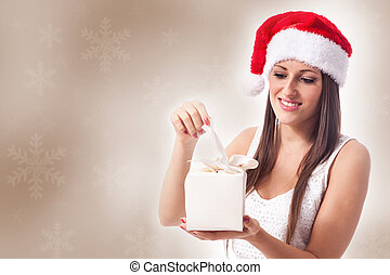 Woman with christmas gift - beautiful woman is opening a...