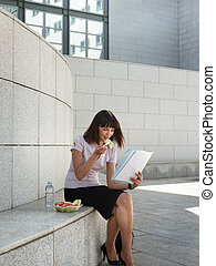 business person eating lunch outside office and reading...