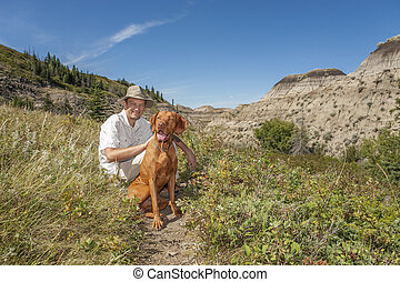 man with dog in badlands