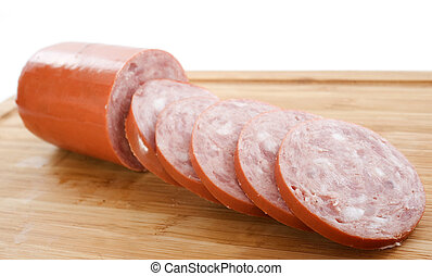 garlic sausage on a cutting board in front of white...
