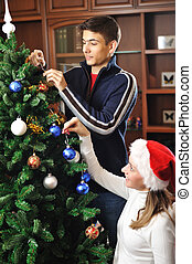 Decorating christmas tree - Young couple decorating...