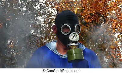Man in gas mask in fog - Smoke rising behind a man in a gas...