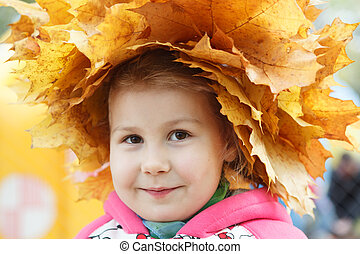 Child happy face with yellow maples wreath