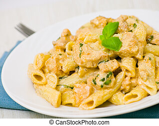 Penne pasta with chicken meat, cream sauce and basil