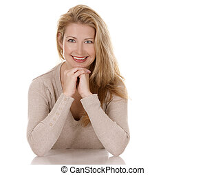 casual woman - pretty blond woman wearing beige top sitting...