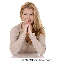 casual woman - pretty blond woman wearing beige top sitting...