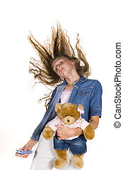 Young Girl dancing with Teddy Bear and portable music player...